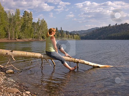 Woman Enjoying Mountain Lake stock photo, This woman is sitting on a tree log while enjoying a leisurely moment at a beautiful mountain lake. by Valerie Garner