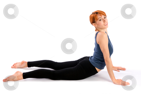 Smiling Fit Woman doing Yoga Exercise stock photo, Smiling relaxed fit woman doing yoga exercise called Bhujangasana, isolated on white background. by Rognar