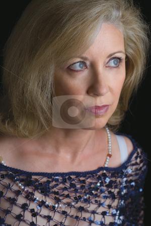 Female model stock photo, Fifty something female model in evening wear looking afar by Yann Poirier