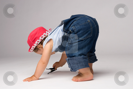 Little Girl Playing stock photo, One year old girl dressed in jeans playing on the floor. by Rognar