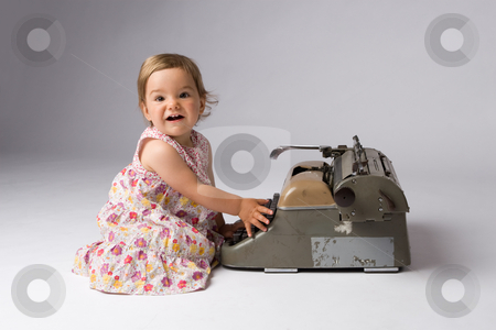 Joyful Baby Girl and Her Toy stock photo, Cute joyful baby girl having fun with an antique typewriter. by Rognar