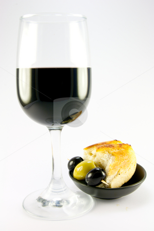 Olives with Crusty Bread and Red Wine stock photo, Glass of red wine with three green olives and crusty bread in a small black bowl on a plain background by Keith Wilson