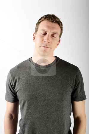 Man with Eyes Closed stock photo, A man is standing in a room with his eyes closed.  He is looking tired.  Vertically framed shot. by Zee Images