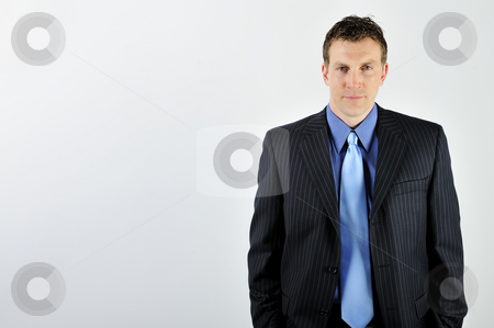 Man Wearing Suit stock photo, A young man is wearing a suit and a blue tie.  He is looking at the camera.  Horizontally framed shot. by Zee Images