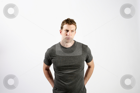 Man Standing in Room stock photo, A young man is standing in a room.  He is looking away from the camera.  Horizontally framed shot. by Zee Images