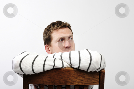 Man Sitting on Chair stock photo, A young man is sitting backwards on a chair and looking away from the camera.  Horizontally framed shot. by Zee Images