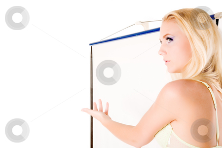 Waist shot lingery model presenting stock photo, Lingery model standing next to a white projector screen.