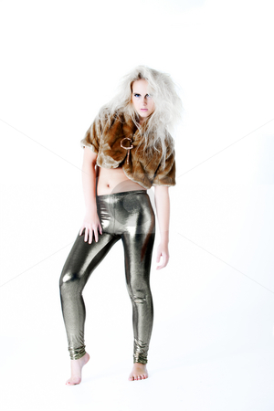 High fashion pose with wild outfit stock photo, Model in refelcting legging, fur and with wild hair looking at the viewer.Usable for health and beauty, cosmetics, love, hate and emotional issues. by Frenk and Danielle Kaufmann