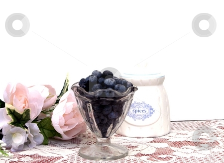 Blueberries stock photo, Bowl of blueberries with roses in the background and space for copy by Shirley Mathews