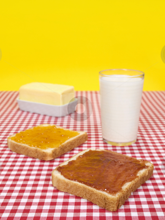 Quick breakfast stock photo, Two slices of bread spread with jam, a glass of milk and a butter stick. by Ignacio Gonzalez Prado