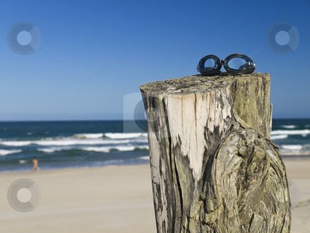 Goggles stock photo, A pair of goggles sitting over a log in the beach. by Ignacio Gonzalez Prado