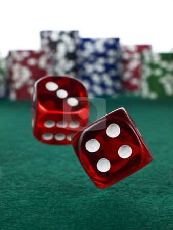 Betting with dices stock photo, Two red dices rolling over a green felt. Out of focus stack of colorful chips on the background. by Ignacio Gonzalez Prado