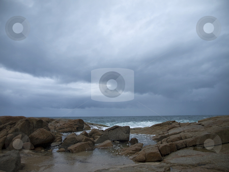 Stormy wheather stock photo, The storm threatens the rocky beach. The storm has already begun on the background. by Ignacio Gonzalez Prado