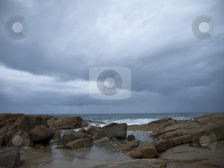 Stormy wheather stock photo, The storm threatens the rocky beach. The storm has already begun on the background. by Ignacio Gonzalez Prado