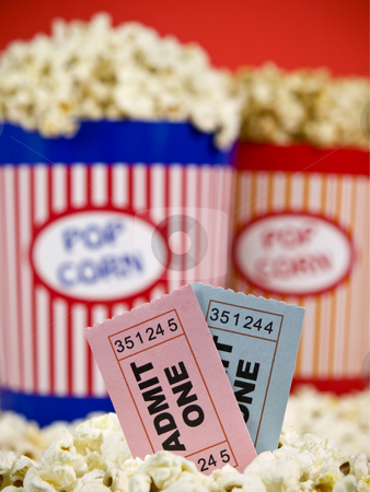 Tickets and fun stock photo, Two popcorn buckets over a red background. Movie stubs sitting over the popcorn. by Ignacio Gonzalez Prado