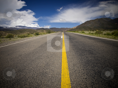 Follow the yellow line stock photo, A desert road by the mountains surrounded by colorful nature. by Ignacio Gonzalez Prado