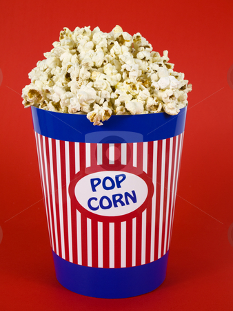 Blue popcorn bucket stock photo, A popcorn bucket over a red background. by Ignacio Gonzalez Prado