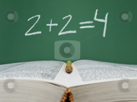 Basic sum stock photo, 2 + 2 = 4 written on a chalkboard with an open book and a pencil on foreground. by Ignacio Gonzalez Prado