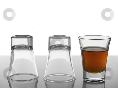 Three in a row stock photo, Two empty shots upside down and a third one full of liquor. by Ignacio Gonzalez Prado