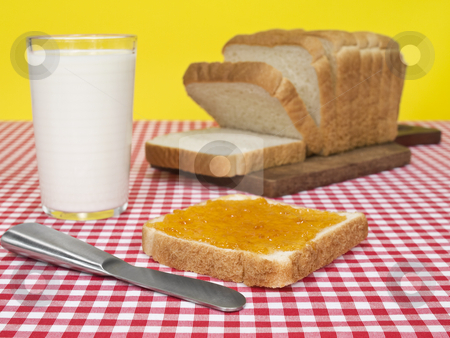 Quick breakfast stock photo, A slice of bread spread with jam beside a loaf of bread and a glass of milk. by Ignacio Gonzalez Prado