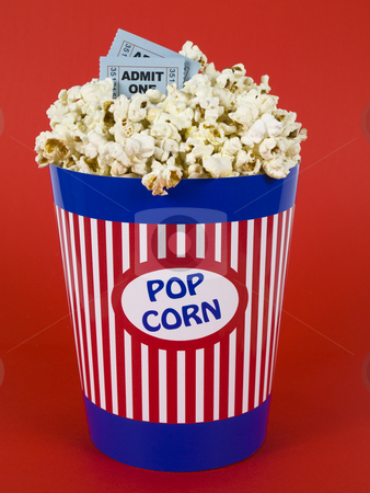 Popcorn and movies stock photo, A popcorn bucket over a red background. Movie stubs sitting over the popcorn. by Ignacio Gonzalez Prado