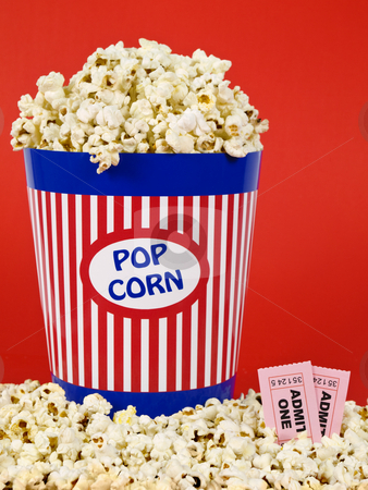 Movie for two stock photo, A popcorn bucket over a red background. Movie stubs sitting over the popcorn. by Ignacio Gonzalez Prado