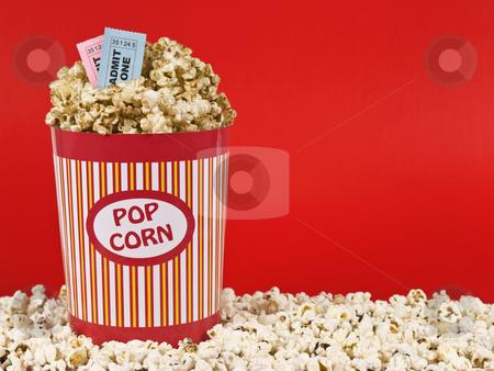 Sweet movie stock photo, A popcorn bucket over a red background. Movie stubs sitting over the popcorn. by Ignacio Gonzalez Prado