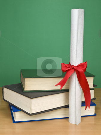 Graduation day stock photo, A pile of books and a diploma. Blank chalkboard on the background. by Ignacio Gonzalez Prado