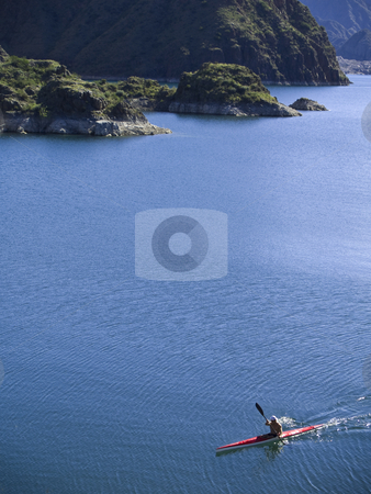 Kayak stock photo, A kayaker paddling across a peaceful lake. by Ignacio Gonzalez Prado