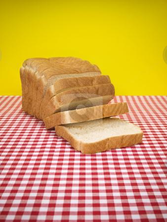 Sliced bread stock photo, Sliced loaf of bread over the table. by Ignacio Gonzalez Prado