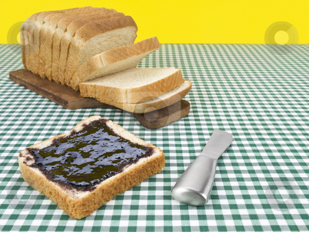 Breakfast time stock photo, A slice of bread spread with jam beside the loaf of bread. by Ignacio Gonzalez Prado