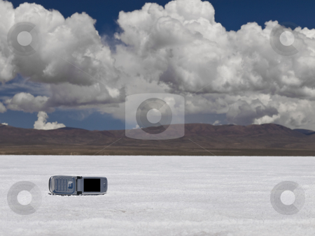 Hanging on stock photo, A cell phone  abandoned on a salt field. Mountains on the background. by Ignacio Gonzalez Prado