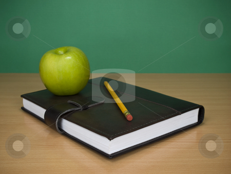 Learning schedule stock photo, A green apple over an agenda. A blank chalkboard as background. by Ignacio Gonzalez Prado