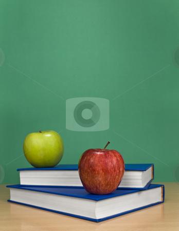 Blank chalkboard stock photo, A blank chalkboard with apples over books. by Ignacio Gonzalez Prado
