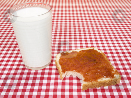 Bite me stock photo, A glass of milk and a toast spread with jam, with a bite missing. by Ignacio Gonzalez Prado
