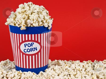 Popcorn bucket stock photo, A popcorn bucket over a red background. by Ignacio Gonzalez Prado