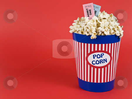 Movies for two stock photo, A popcorn bucket over a red background. Movie stubs sitting over the popcorn. by Ignacio Gonzalez Prado