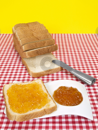 Bread and jam stock photo, A slice of bread spread with jam beside a loaf of sliced bread. by Ignacio Gonzalez Prado