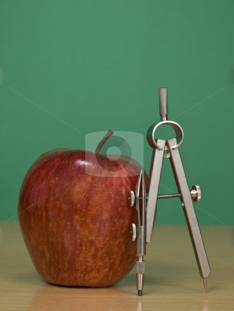 Healthy learning stock photo, A red apple and a drawing compass over a classroom desk. Blank chalkboard on the background. by Ignacio Gonzalez Prado