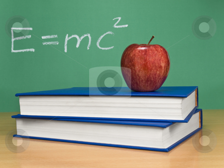 Theory of relativity stock photo, Einsteins formula of theory of relativity on a chalkboard. An apple over books on foreground. by Ignacio Gonzalez Prado
