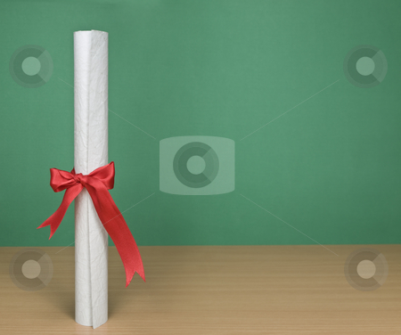 Diploma and chalkboard stock photo, A blank chalkboard with a diploma on forefround. by Ignacio Gonzalez Prado