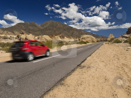 Lonely trip stock photo, A fast car on the road in a arid and rocky landscape. by Ignacio Gonzalez Prado