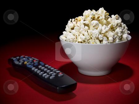 Movies at home stock photo, A popcorn bowl and a remote control ready for fun. by Ignacio Gonzalez Prado
