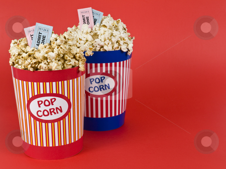 Four for the movies stock photo, Two popcorn buckets over a red background. Movie stubs sitting over the popcorn. by Ignacio Gonzalez Prado