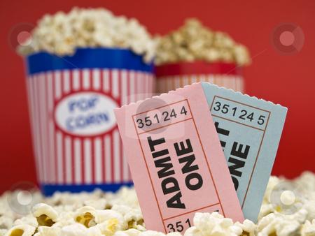 Movie stubs and popcorn stock photo, Two popcorn buckets over a red background. Movie stubs sitting over the popcorn. by Ignacio Gonzalez Prado