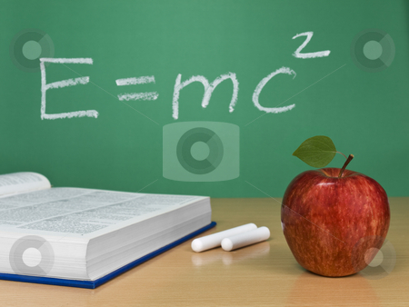 E=mc2 stock photo, Einstein's formula on a chalkboard with an apple, a book and some chalks. by Ignacio Gonzalez Prado