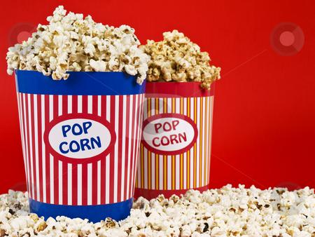Two popcorn buckets stock photo, Two popcorn buckets over a red background. by Ignacio Gonzalez Prado
