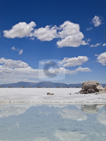 Magic mirror stock photo, A rock sitting aside a small pool with water in a huge salt field. by Ignacio Gonzalez Prado