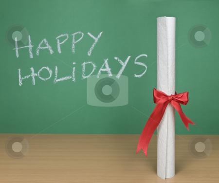Happy holidays stock photo, Happy holidays written on a chalkboard with a diploma on forefround. by Ignacio Gonzalez Prado