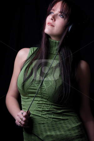 Fashion model - listening to music stock photo, Twenty something fashion model listening to music with big headphone by Yann Poirier